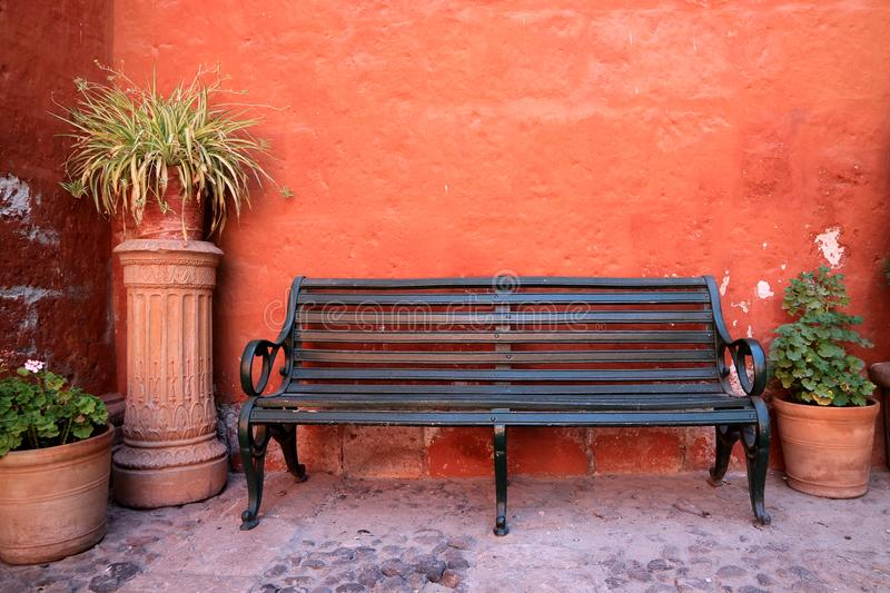 Black wooden bench in front of orange color rough wall with many terracotta planters, Santa Catalina Monastery in Arequipa royalty free stock photo