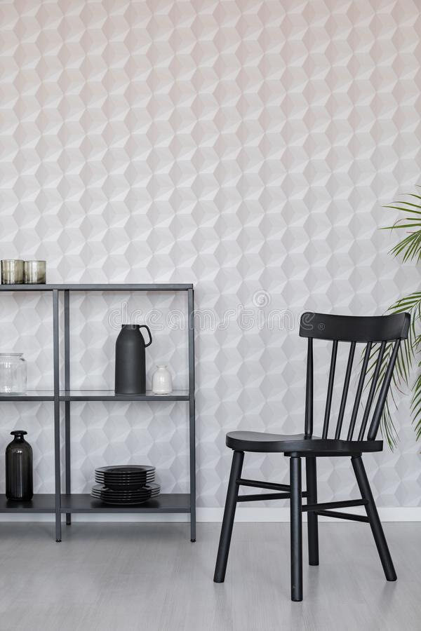 Black wooden chairs next to metal shelf with vases, plate and accessories on empty wall wall with unique wallpaper, real photo vector illustration