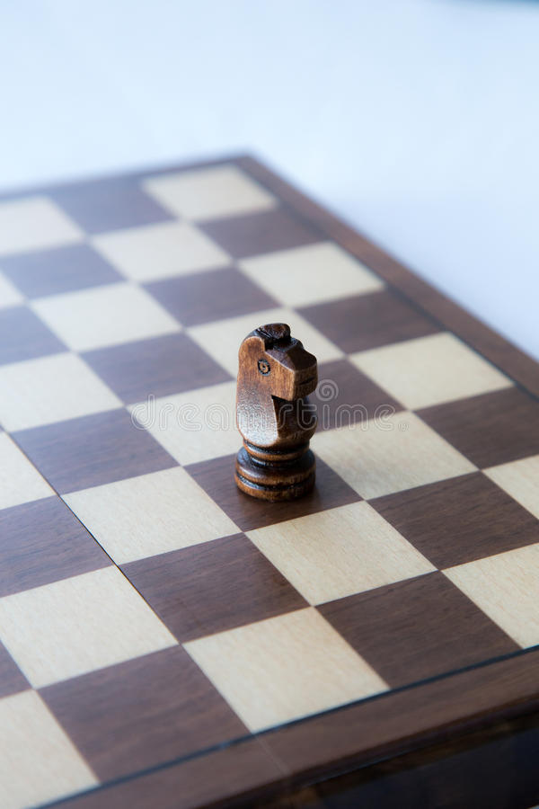 Black Wooden Chess Knight. A single chess knight on top of the chessboard, still life, board game stock images