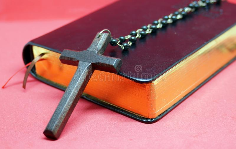 Black wooden cross with chains on bible book. stock photo