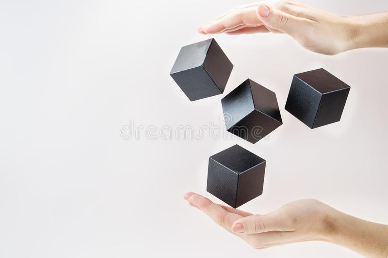 Black wooden cubes are floating. On open woman hand. Concept of creative, logical thinking. Abstract background with cubes with copy space. Shape floating royalty free stock photo