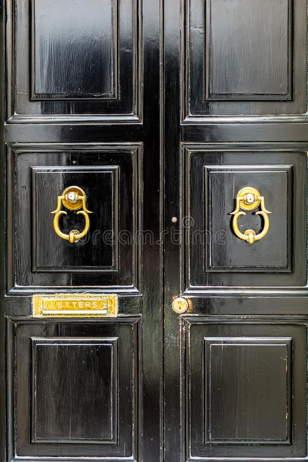 Black wooden door with golden vintage knockers and mail slot letterbox stock image