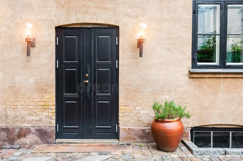 Black wooden door and street lamps on the house. Denmark, Europe stock photos