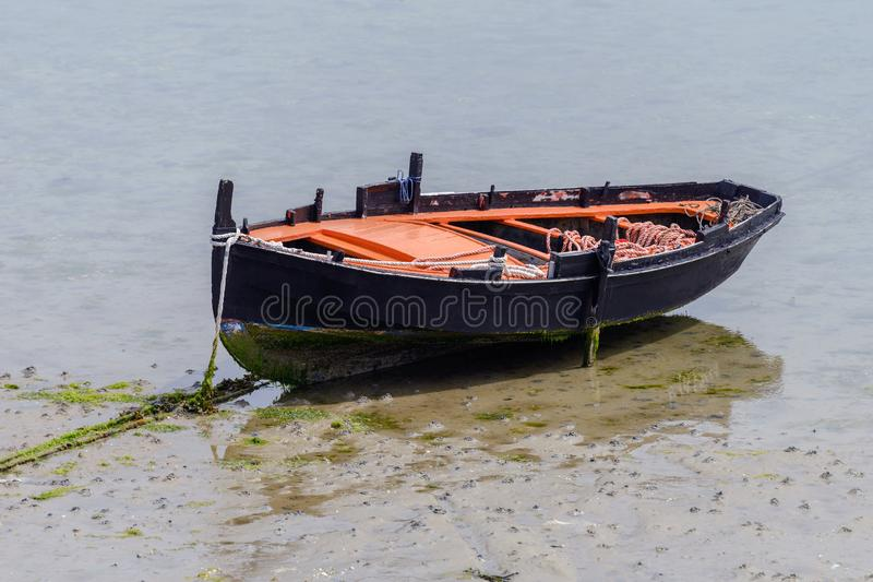 Black wooden fishing boat moored on the shore. Image of black wooden fishing boat moored on the shore royalty free stock image