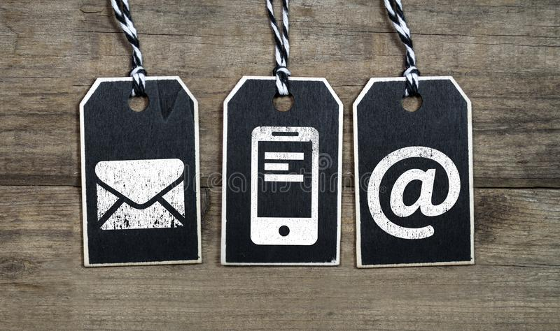Black wooden hang tag with customer support icons royalty free stock photos