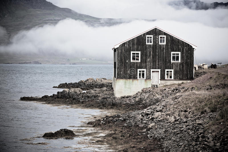 Black wooden house in east iceland royalty free stock for Iceland lonely house