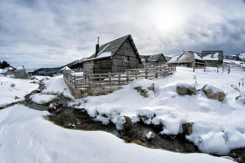 Black Wooden House Surrounded by Snow Under White Clouds stock images