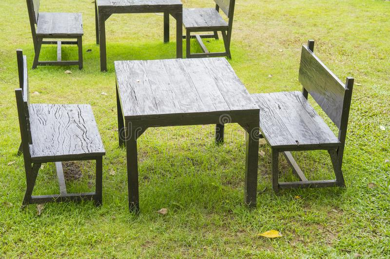 Black Wooden table and seat isolated on green grass background stock image