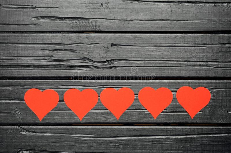 Black wooden textured background with red hearts. royalty free stock photo