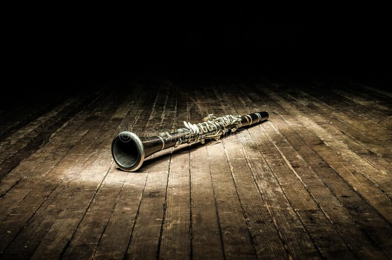 A black woodwind clarinet lies on a dark brown wooden stage in the rays of light royalty free stock image
