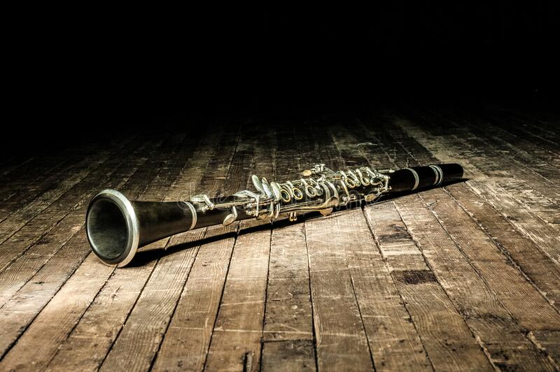 black woodwind clarinet lies on a brown wooden stage royalty free stock image