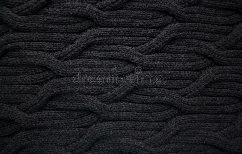 Black woolen cable knit pattern. Abstract background stock images