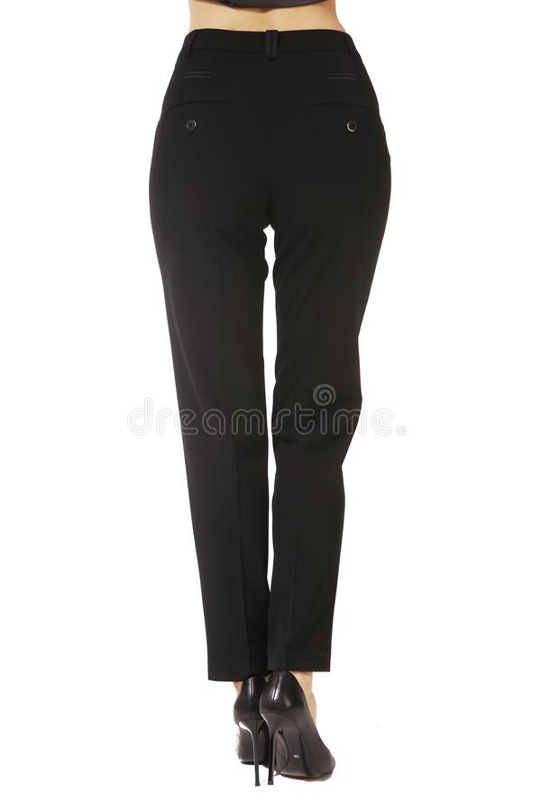 Black woolen official trousers on model legs with white stiletto heels. With bare toes stock photo