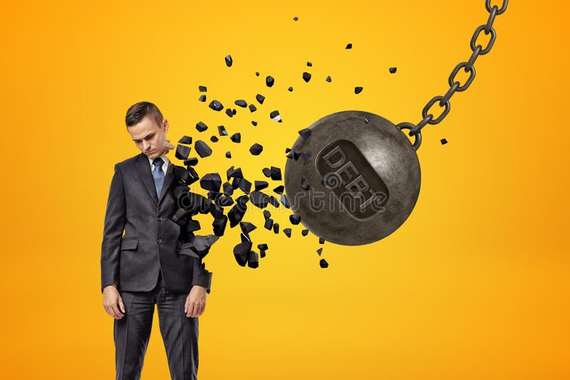 Black wrecking ball with word DEBT on it hitting sad young businessman and breaking half of his body in pieces. stock photos
