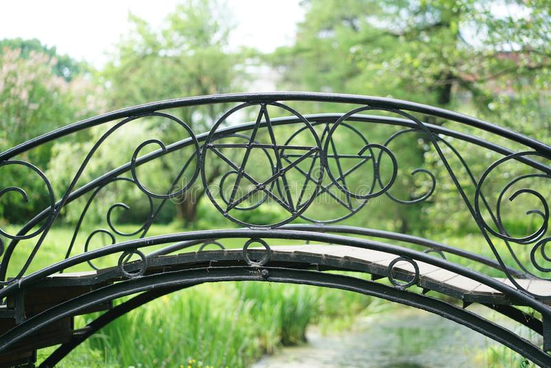 Black wrought iron bridge with goth pentagram star inside. summer day photo. nobody. Magic theme stock photo