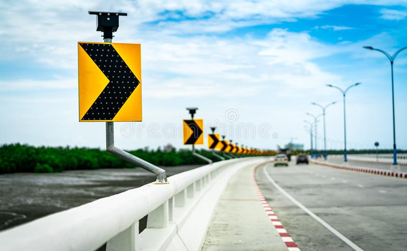 Black and yellow arrow on curve traffic sign on the bridge with solar cell panel ob blurred background of concrete road and car royalty free stock photos