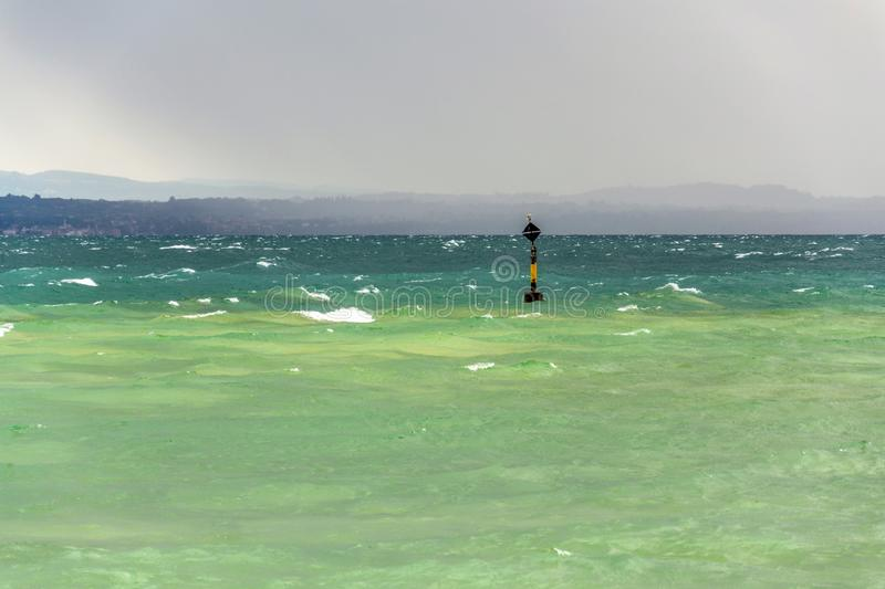 Black and yellow buoy in turbulent blue green waves on Lago di Garda lake, windy, cloudy, foggy weather, Sirmione. Italy royalty free stock photography