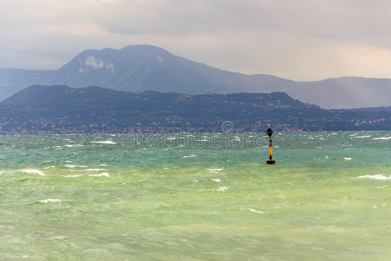 Black and yellow buoy in turbulent blue green waves on Lago di Garda lake, windy, cloudy, foggy weather, Sirmione. Italy royalty free stock images