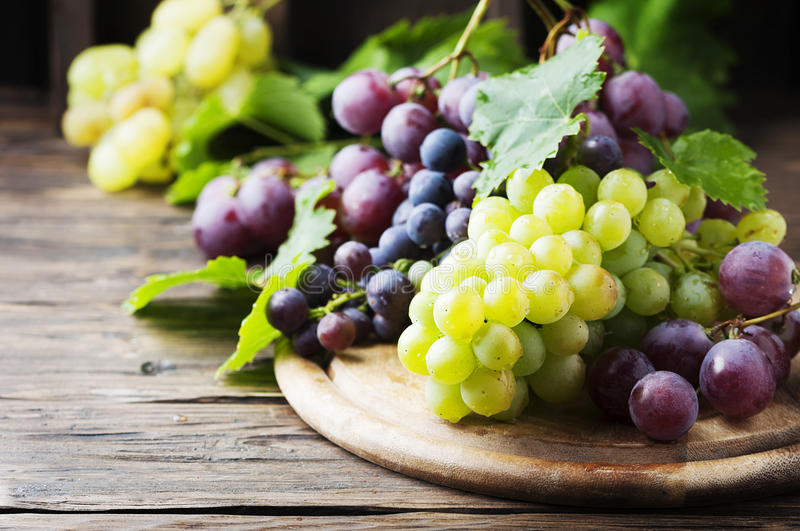 Black and yellow grape on the wooden table royalty free stock images