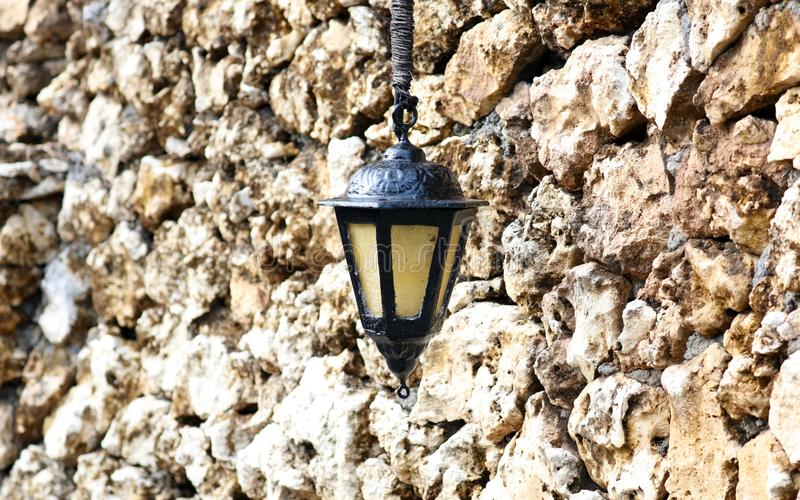 Black and yellow lamp in Bali Indonesia with rocky wall in background royalty free stock photos