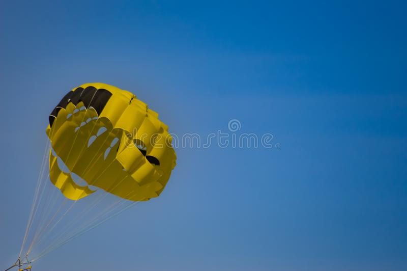 Black and yellow parachute. On a blue sky background stock photography