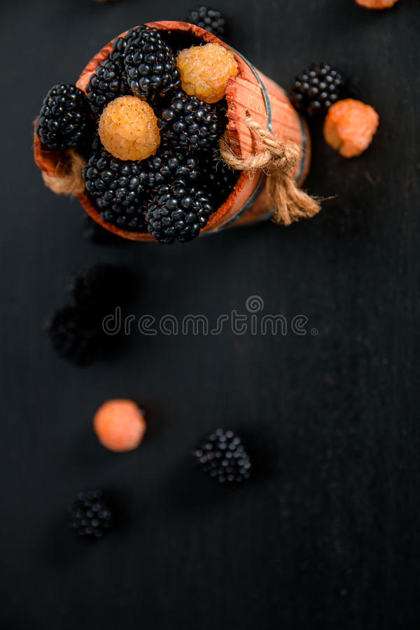 Black and yellow raspberries in a wooden basket on background. Frame. Copy space. Top view. Black and yellow raspberries in a wooden basket on black wooden stock photo