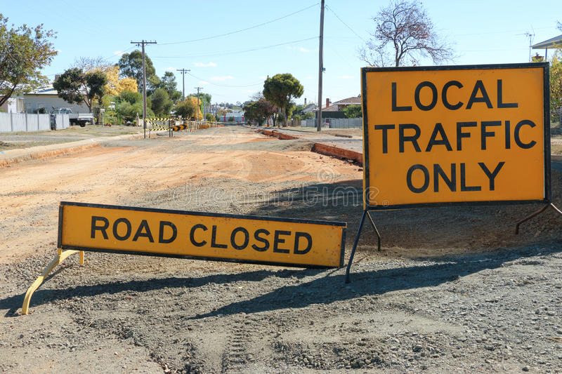 Black and yellow Road Closed - Local Traffic Only signs. And road under construction royalty free stock photo