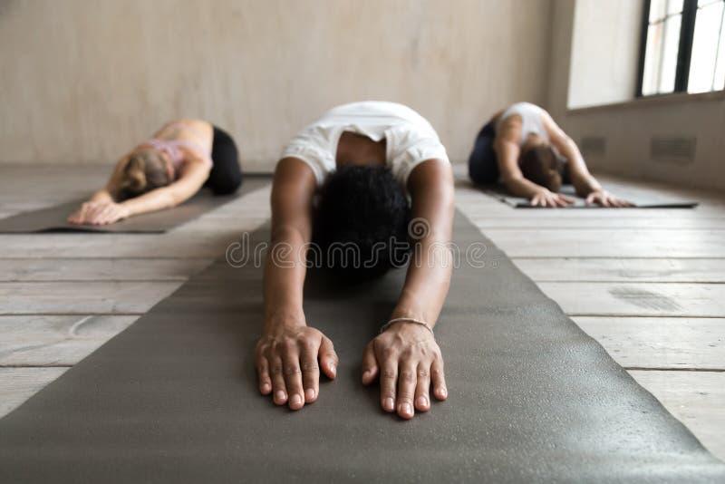 Black yogi woman and group of people doing Balasana exercise. Black sporty young yogi women doing yoga Child exercise, Balasana pose, working out, indoor close stock image