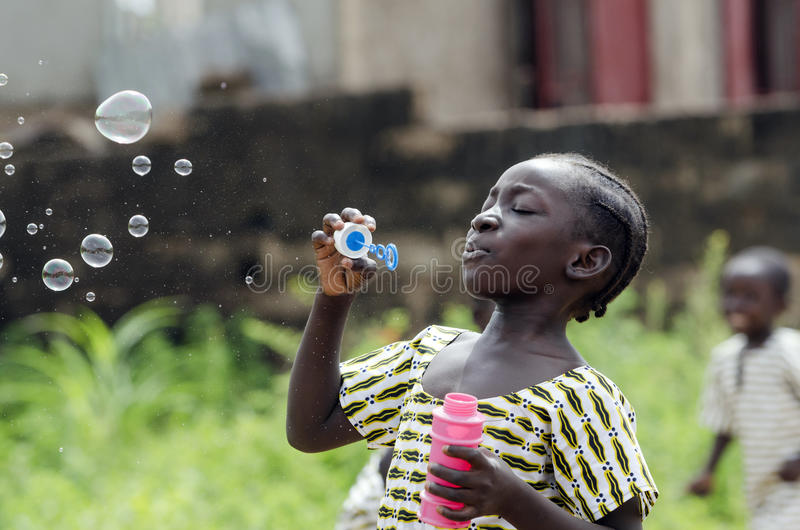 Black young beautiful girl having fun outdoors blowing soap bubbles. Happiness symbol. Elementary student happy outside her royalty free stock image