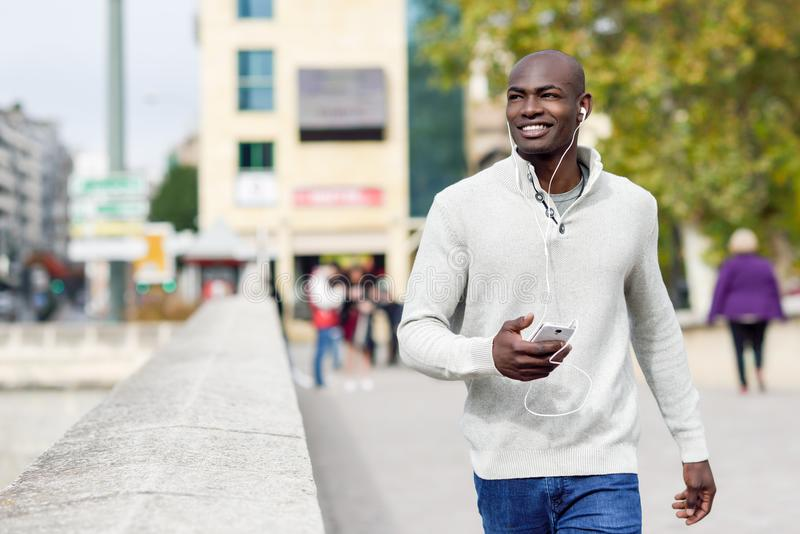 Black young man with a smartphone in his hand in urban background royalty free stock photography