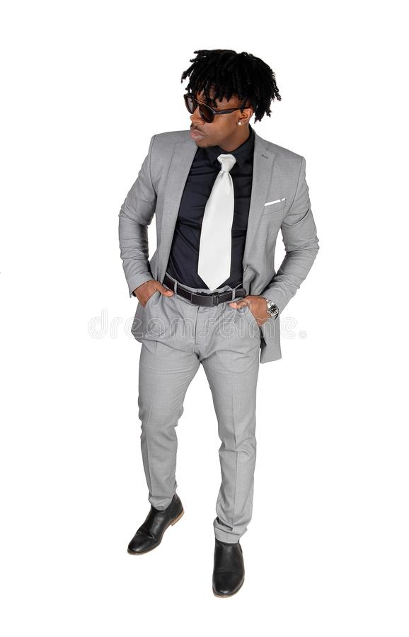 A black young man standing in a gray suit and sunglasses royalty free stock photos