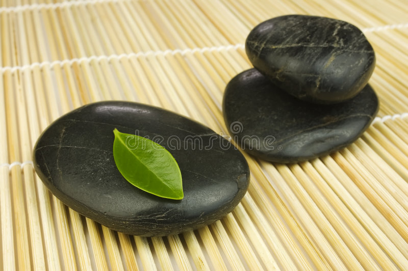 Black zen pebbles and green leaf. Row and pile of black zen pebbles and a young green leaf on bamboo mat. Alternative therapy and new life symbol stock image