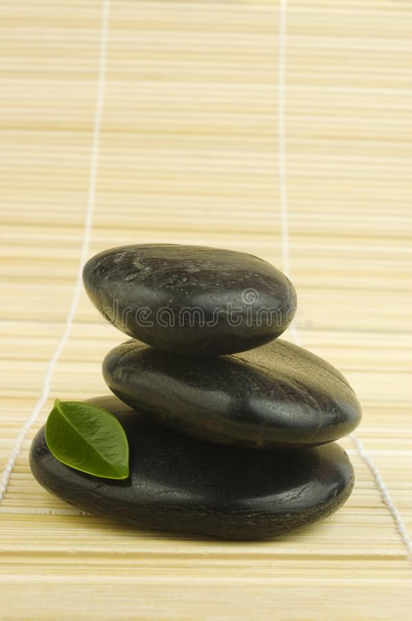 Black zen pebbles and green leaf on bamboo royalty free stock photos