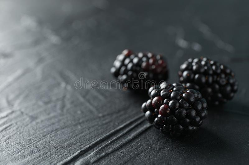 Blackberries on black cement background, closeup. And space for text stock photo