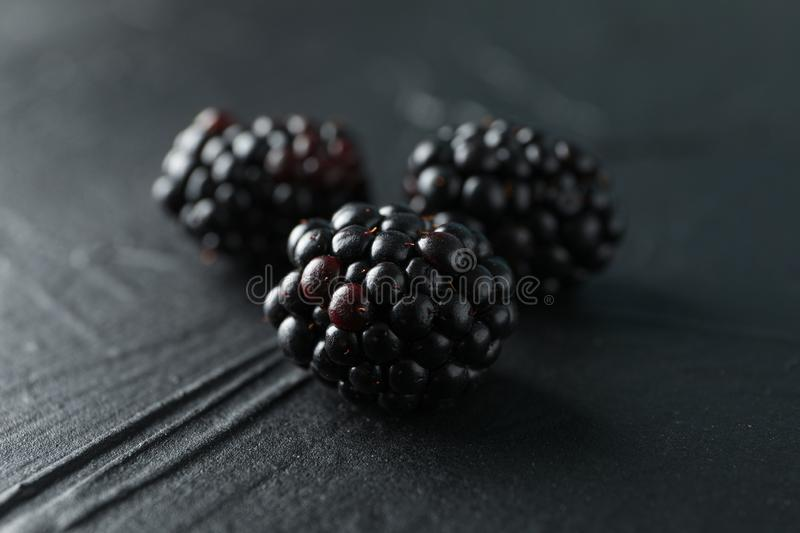 Blackberries on black cement background, closeup. And space for text stock photos