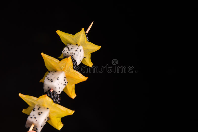 Blackberries, carambola and pitaya on a wooden stick on a black background. Homemade finger food with fruits for snack. stock images
