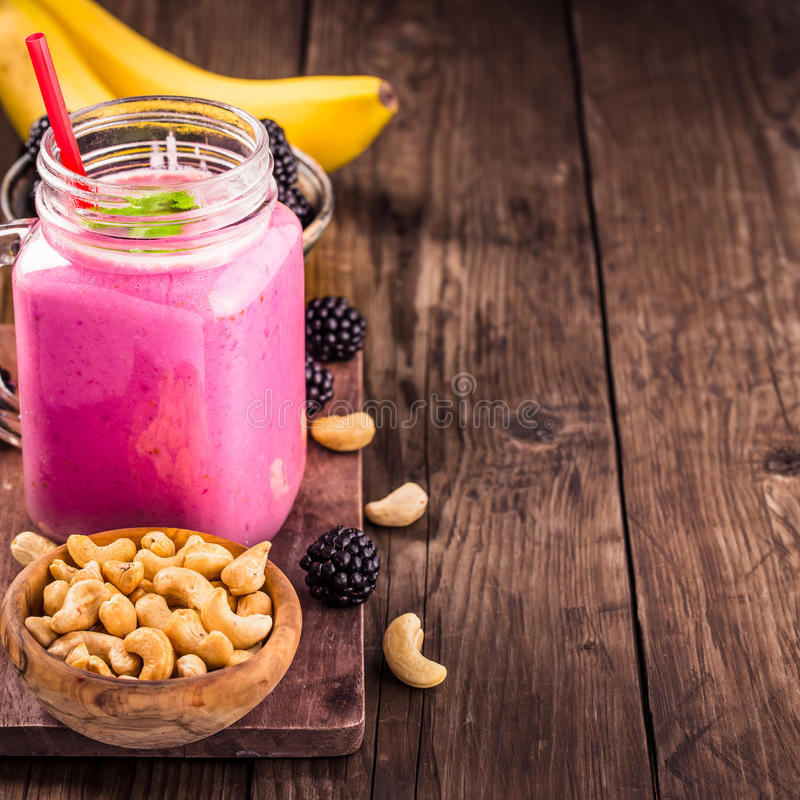 Blackberry banana cashew smoothie with copy space. Mason jar of blackberry banana smoothie with cashew milk. With copy space royalty free stock image