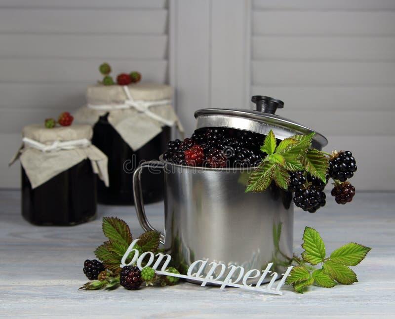Blackberry dans une tasse et une confiture en métal avec un appetit de fève d'inscription images libres de droits