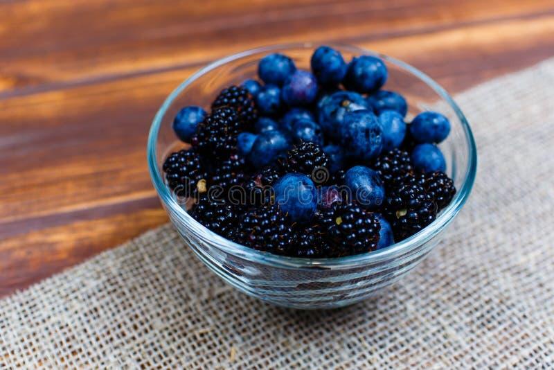 Blackberry en moerasblauwe bosbes in kleine glaskom stock afbeeldingen