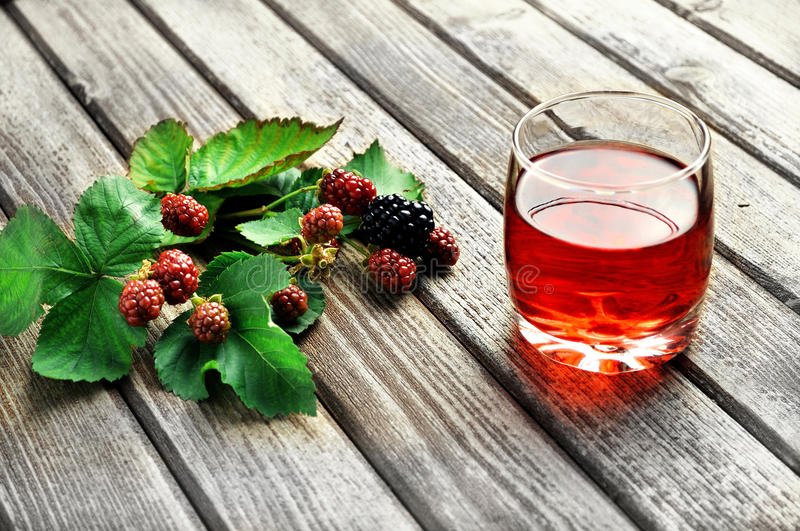 Blackberry juice. A glass of blackberry juice on a rustic table stock images