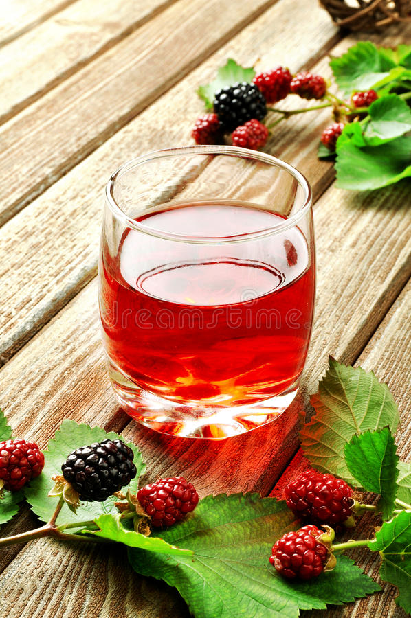 Blackberry juice. A glass of blackberry juice on a rustic table stock photo