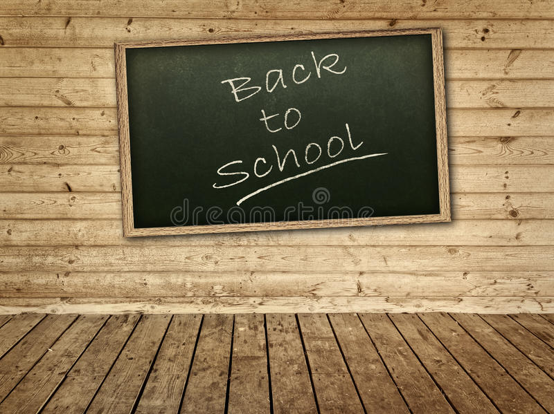 Blackboard. With back to school inscription on the wooden wall royalty free stock photos
