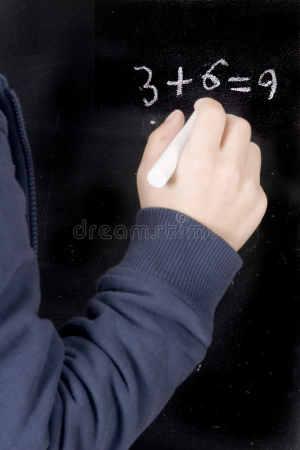 Blackboard. A boy is writing a sum on the blackboard stock photography