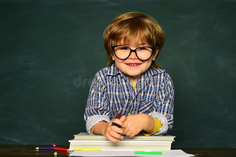 Blackboard background - copy space. Cheerful smiling child at the blackboard. School children stock photo