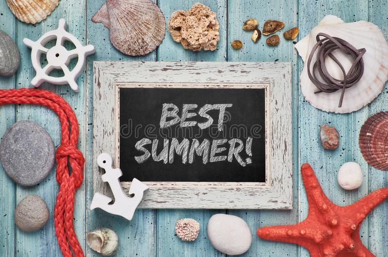 Blackboard with `Best summer` chalk text, with sea shells, rope and star fish. On light green wooden background royalty free stock images