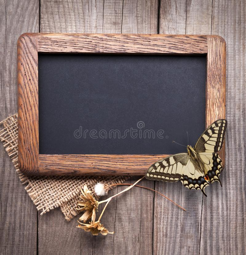 Blackboard empty decorated with dried flowers on the old wooden table stock photos