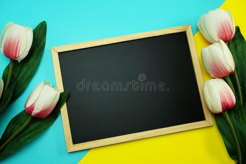 Blackboard i wiązka tulipanowy kwiat na tła mieszkaniu nieatutowym błękitnym i żółtym zdjęcia royalty free