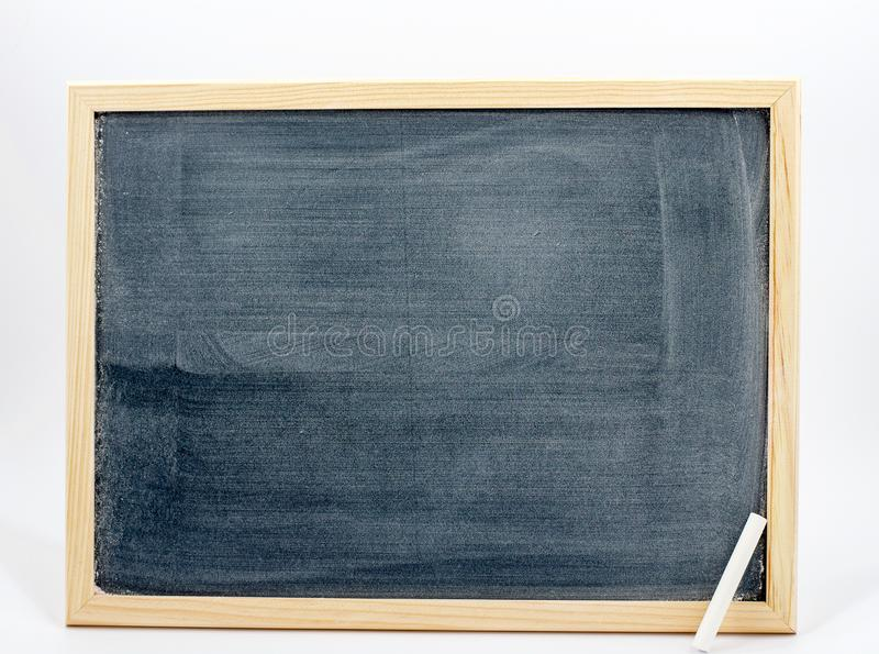 Blackboard isolated on a white background with a white chalk in the corner. Blackboard to write and education, to learn to calculate. a white chalk is in the stock photo
