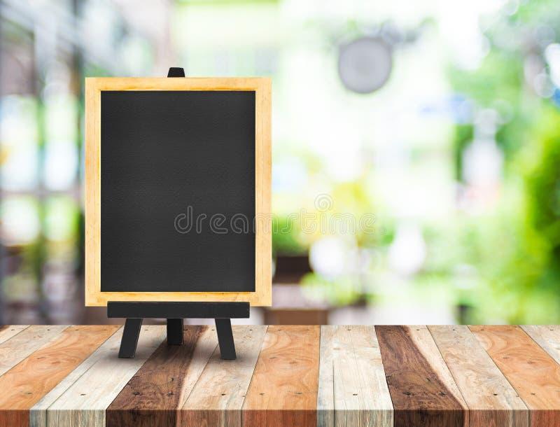 Blackboard menu z sztalugą na drewnianym stole z plamy sklep z kawą zdjęcia stock