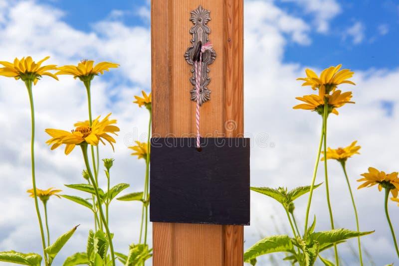 Blackboard obwieszenie na kluczu przed żółtymi kwiatami zdjęcie stock